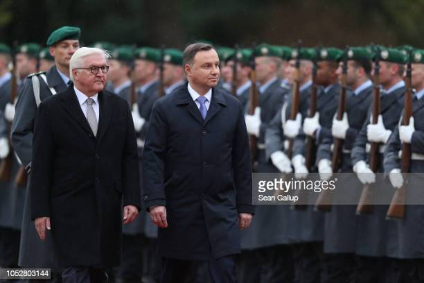 Polish President Andrzej Duda and German President Frank-Walter Steinmeier review a guard of honor under a light rain at Schloss Bellevue...
