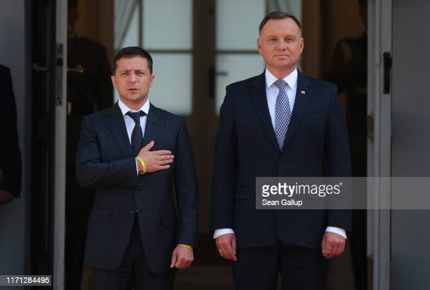Polish President Andrzej Duda and Ukrainian President Volodymyr Zelensky listen to their nations' national anthems upon Zelensky's arrival at the...