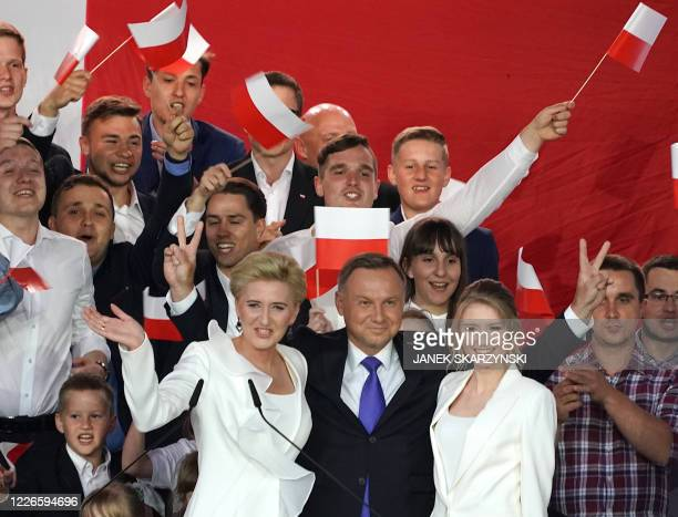 Polish President Andrzej Duda flashes V-signs after addressing supporters with his wife Agata as exit poll results were announced during the...