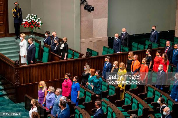 TOPSHOT Polish President Andrzej Duda is standing next to his wife Agata as left wing parliamentarians are seen dressed in colors of the rainbow...