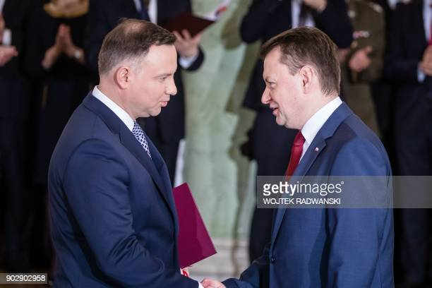Polish President Andrzej Duda shakes hands with newlyappointed Defence Minister Mariusz Blaszczak on January 9 2018 during a ceremony at the...