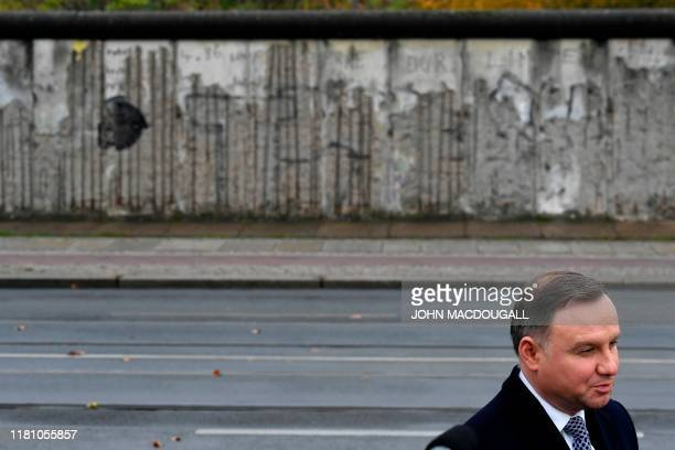 Polish President Andrzej Duda speaks to the press in front of remains of the Berlin Wall after laying flowers at the Visegrad Monument during...
