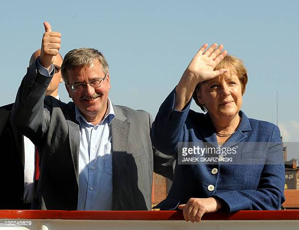 Polish President Bronislaw Komorowski and German Chancellor Angela Merkel wave to the people gathered in Gdansk harbour on July 9 2011 Merkel and her...