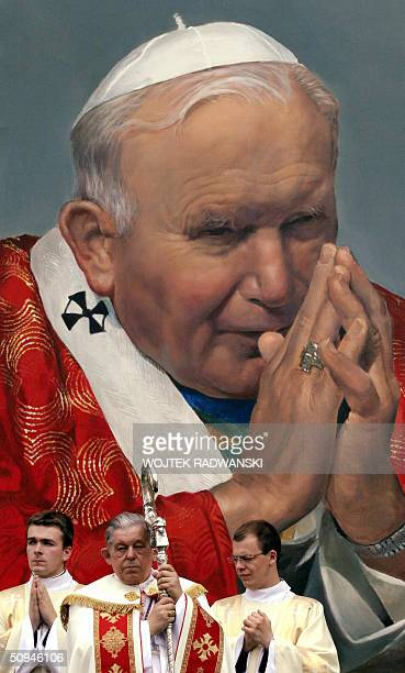 Polish Primate Cardinal Jozef Glemp stands in front of a huge portrait of Pope John Paul II during a Corpus Christi Procession in Warsaw 10 June 2004...