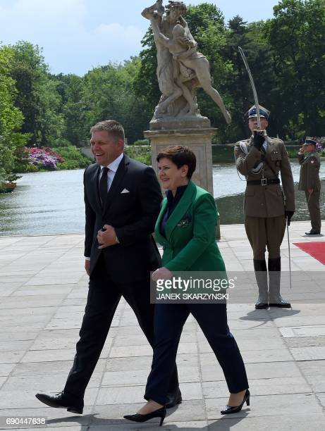 Polish Prime Minister Beata Szydlo and Slovak Prime Minister Robert Fico share a laugh during a welcoming ceremony at the Palace on the Isle in...