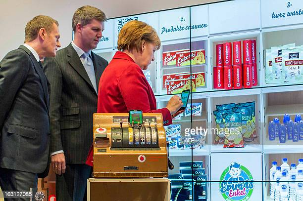 Polish Prime Minister Donald Tusk and Stephan Weil, Prime Minister of Lower Saxony watch as German Chancellor Angela Merkel tries a product scanner...