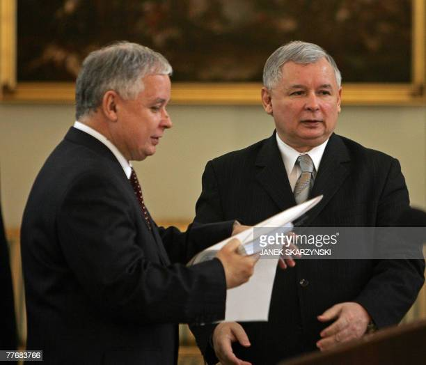 Polish Prime Minister Jaroslaw Kaczynski hands his resignation documents to his twin brother President Lech Kaczynski during a ceremony at the...