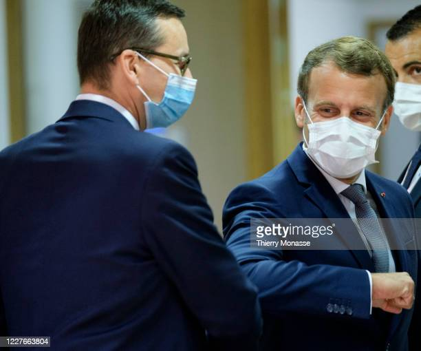 Polish Prime Minister Mateusz Morawiecki elbow bumps French President Emmanuel Macron during an EU summit on July 17, 2020 in Brussels, Belgium....