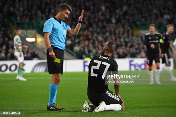 Polish referee Pawel Gil gestures to Rosenborg's Tunisian striker Issam Jebali before showing him a yellow card for simulation during the UEFA Europa...