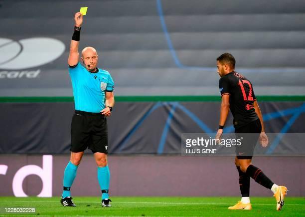 Polish referee Szymon Marciniak presents a yellow card to Atletico Madrid's Brazilian defender Renan Lodi during the UEFA Champions League...