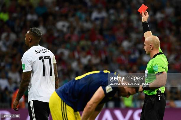 TOPSHOT Polish referee Szymon Marciniak presents Germany's defender Jerome Boateng with a red card during the Russia 2018 World Cup Group F football...