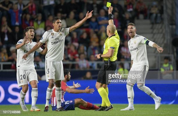 Polish referee Szymon Marciniak shows a yellow card to Real Madrid's Spanish midfielder Marco Asensio as Atletico Madrid's Spanish forward Diego...