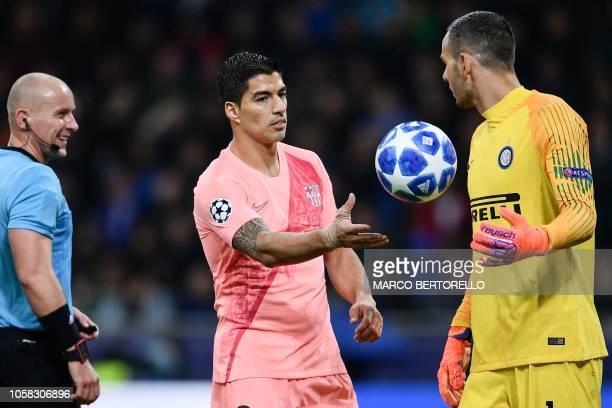 Polish referee Szymon Marciniak smiles as Barcelona's Uruguayan forward Luis Suarez hands the ball to Inter Milan's Slovenian goalkeeper Samir...