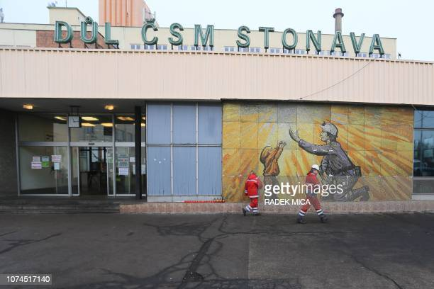 Polish rescue workers walk past a mural mosaic and candles at the coal mine in Stonava near Karviná Czech Republic on December 21 where 13 miners...