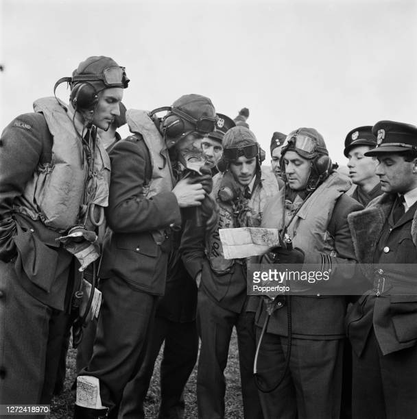 Polish Royal Air Force pilots of No 303 Squadron RAF consult a map with their squadron leader as they prepare for their next sortie from their base...