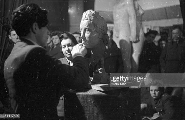 Polish scuptor Tadeusz Koper putting the finishing touches to a sketch model face sculpture at the YMCA Services' Club the Strand London 27th...