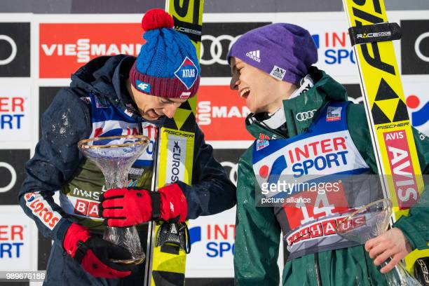Polish ski jumperKamil Stoch and German ski jumper Andreas Wellinger stand on the podium after the second round of the Four Hills Tournament in...