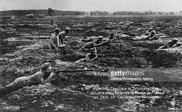 Polish soldiers laying in the mud of the trenches take aim with their rifles against the Russians during World War One circa 1916 Poland allied...
