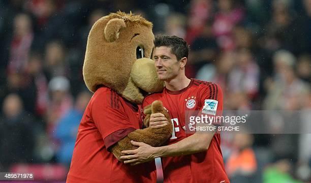 Polish striker Robert Lewandowski celebrate with the Bayern Munich maskot 'Baerli' after the German first division Bundesliga football match FC...
