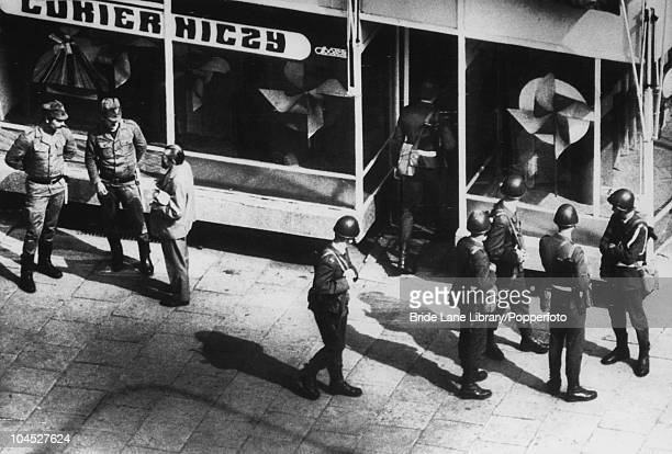 Polish troops check a man's papers while another enters a shop during antigovernment street demonstrations by supporters of the Polish trade union...