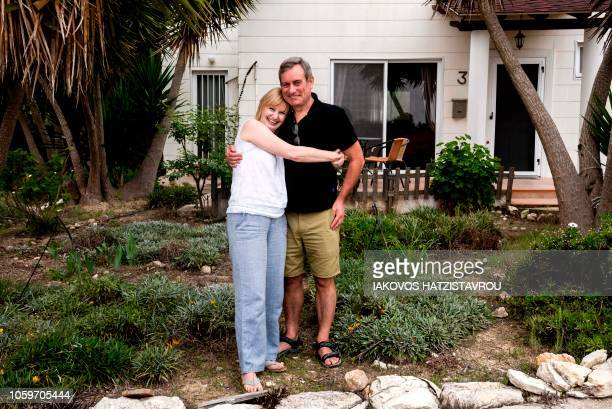 Polish woman Barbara Lovatt poses with her husband Martin at their new home in the village of Polemi near Pafos in Cyprus on October 20 2018 Uk...