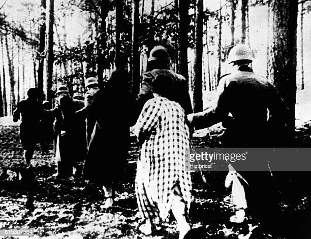 Polish women in Palmiry being led through a forest to their executions by German soldiers, ca. 1939. | Location: Palmiry, Poland.