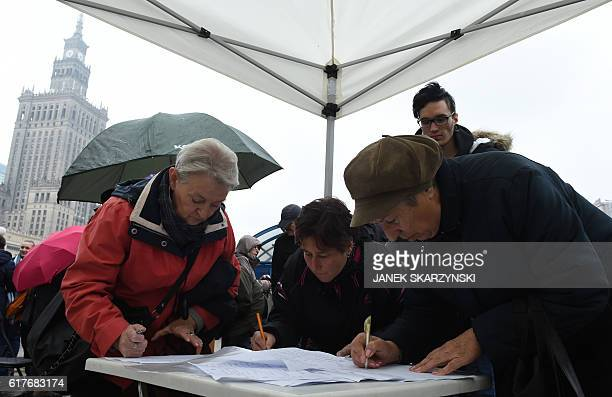 Polish women sign a prochoice petition during a women's rights rally in Warsaw on October 24 2016 Polish women have again donned black and taken to...