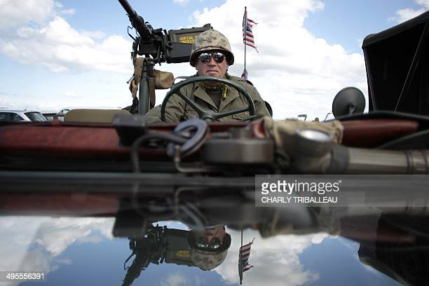 A Polish World War II enthousiast dressed as a WWII US soldier sits in a vintage military jeep in ArromancheslesBains northwestern France on June 4...