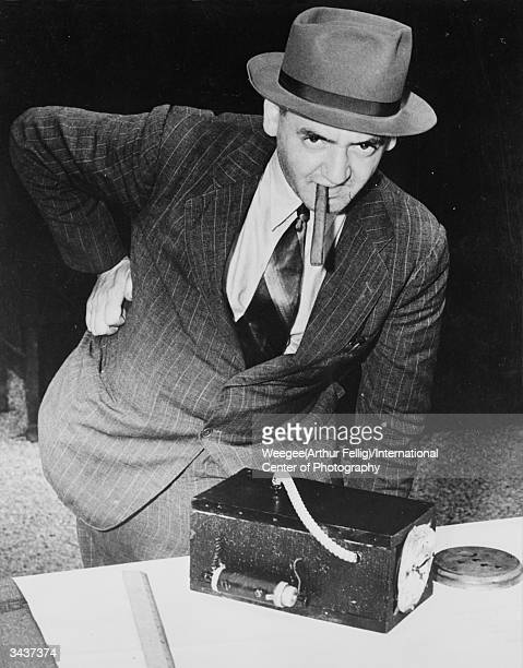 PolishAmerican photographer Arthur 'Weegee' Fellig smokes a large cigar as he examines a homemade bomb at a New York police station Photo by...