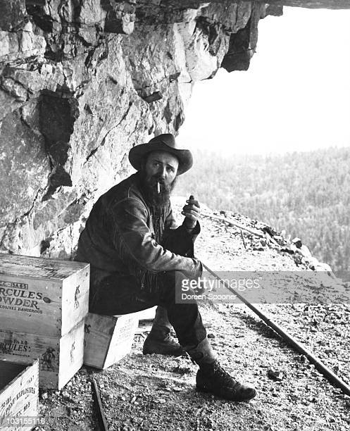 PolishAmerican sculptor Korczak Ziolkowski smokes a cigarette near a crate of dynamite high up on a bluff of the Black Hills on the South...