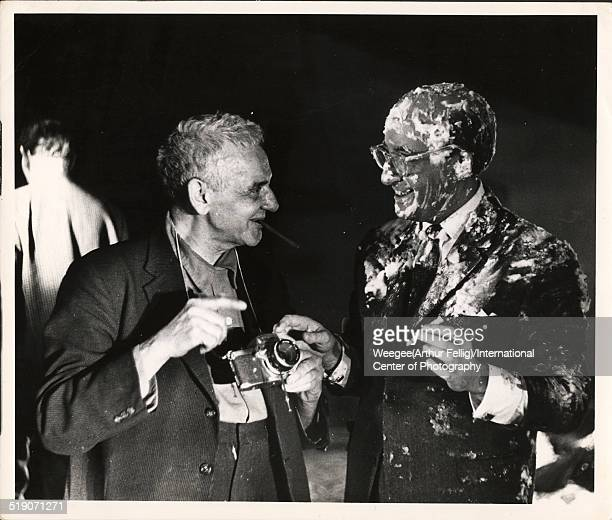 Polishborn American photographer Weegee shows his camera to British actor and comedian Peter Sellers covered in pie filling and in costume as...