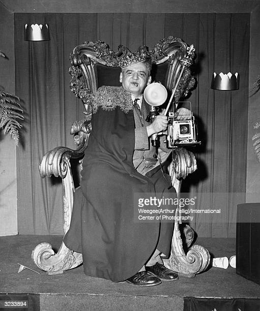 Polishborn newspaper photographer Arthur Fellig better known as Weegee seated on a lavish throne with a crown and sceptre and of course his camera...