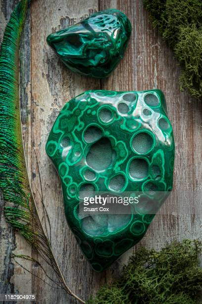 polished malachite surrounded by dried moss on a rustic wooden background with a peacock feather. malachite is a copper carbonate hydroxide mineral. - 孔雀石 ストックフォトと画像