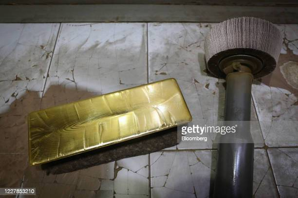 Polishing tool sits alongside a 12.5 kilogram gold ingot at the Uralelectromed Copper Refinery, operated by Ural Mining and Metallurgical Co. , in...