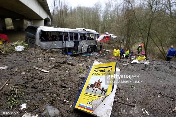 Polish-Russian phrasebook lies on the ground as firefighters work to hoist up a bus after it crashed off the E34 highway near Ranst, Antwerp...