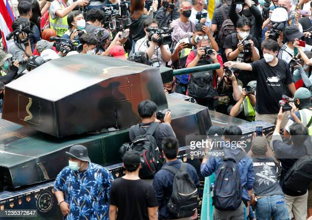 Political activist Sombat Boonngamanong, raises his three finger salute to a mock-up of a tank during a car mob demonstration. More than 1,000 cars...