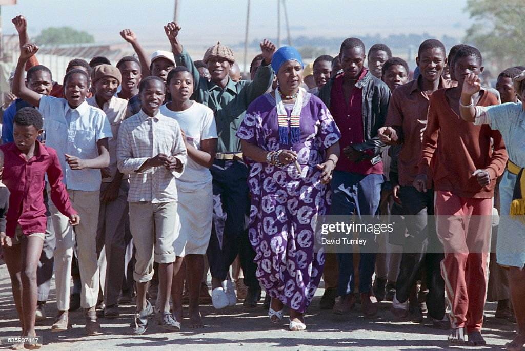 Political activist Winnie Mandela marches with a crowd of youths in the Brandfort Township, from which she was banished for eight years.