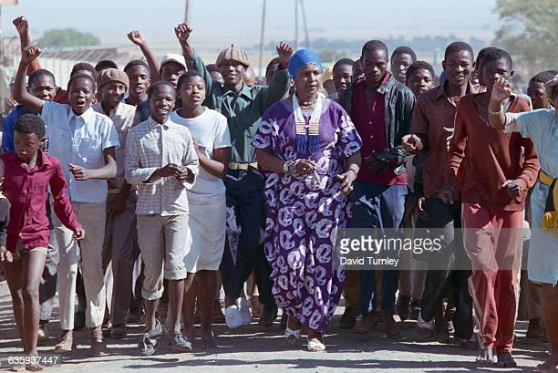 Political activist Winnie Mandela marches with a crowd of youths in the Brandfort Township from which she was banished for eight years