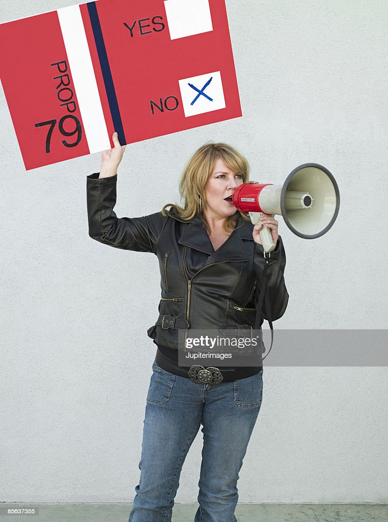Political activist with sign and bullhorn : Stock Photo