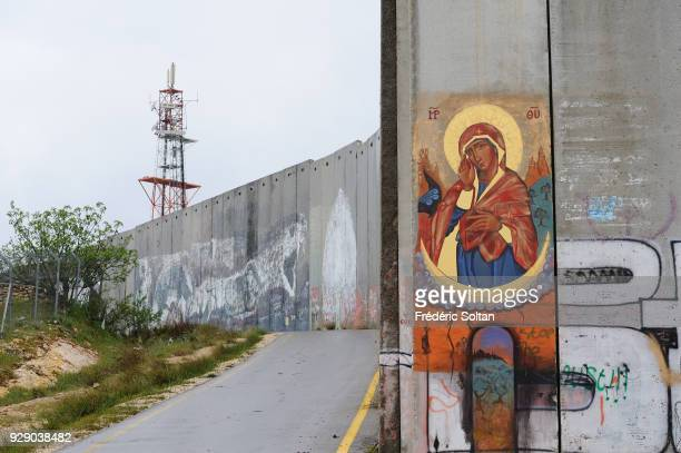 Political and social mural painting and graffitis illustrating the Virgin Mary by a Russian painter of icons on the Israeli West Bank barrier in...