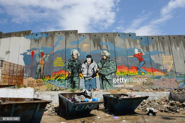 Political and social mural painting and graffitis illustrating the fight between West bank and Israel on the Israeli West Bank barrier in Bethlehem...