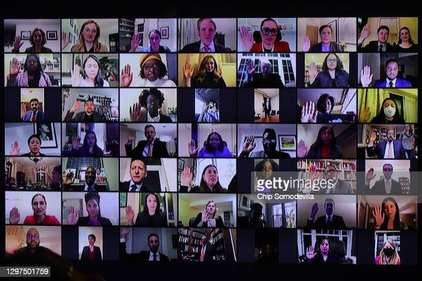 Political appointees to President Joe Biden's administration raise their right hands and are sworn in via Zoom just hours after Biden's inauguration...