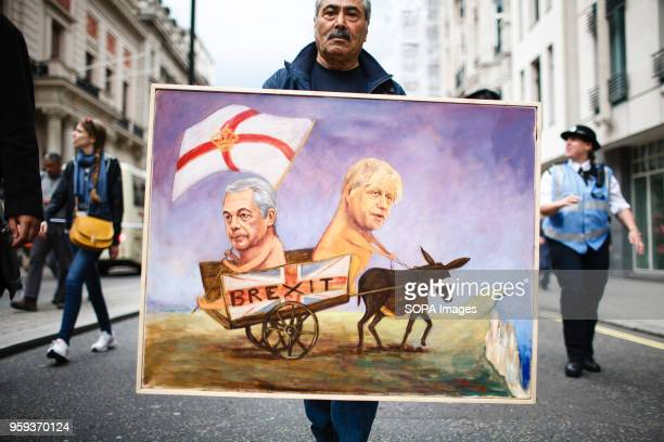 Political artist Kaya Mar carries a painting of 'Brexit' advocates Nigel Farage and Boris Johnson being led off a cliff by a blindfolded donkey...