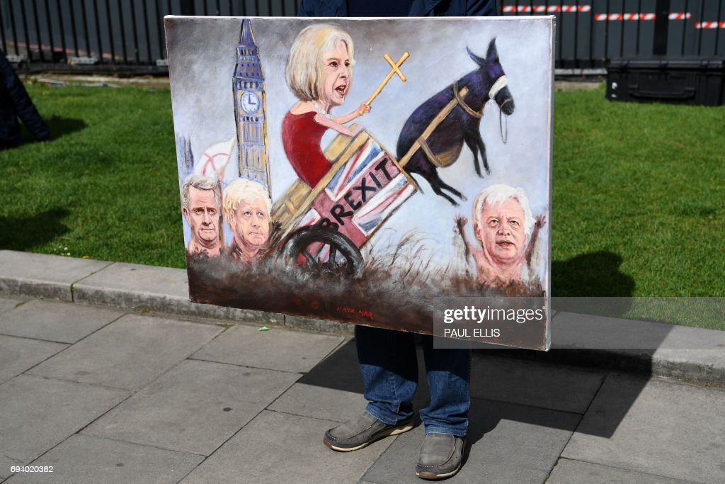 TOPSHOT - Political artist Kaya Mar holds a painting depicting the faces of British Prime Minister Theresa May, British Foreign Secretary Boris Johnson, Britain's Secretary of State for Exiting the European Union (Brexit Minister) David Davis and Britain'sInternational Trade Secretary Liam Fox, as he stands on College Green, opposite the Houses of Parliament in central London on June 9, 2017 as results from a snap general election show the Conservatives have lost their majority. British Prime Minister Theresa May faced pressure to resign on June 9 after losing her parliamentary majority, plunging the country into uncertainty as Brexit talks loom. The pound fell sharply amid fears the Conservative leader will be unable to form a government and could even be forced out of office after a troubled campaign overshadowed by two terror attacks. / AFP PHOTO / Paul ELLIS / RESTRICTED