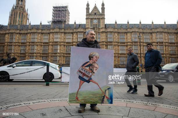 Political artist Kaya Mar poses with a painting depicting British Prime Minister Theresa May and Labour Leader Jeremy Corbyn outside the Houses of...