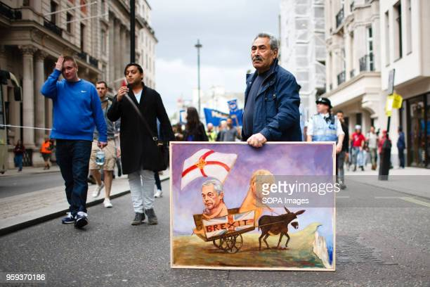 Political artist Kaya Mar stands with a painting of 'Brexit' advocates Nigel Farage and Boris Johnson being led off a cliff by a blindfolded donkey...