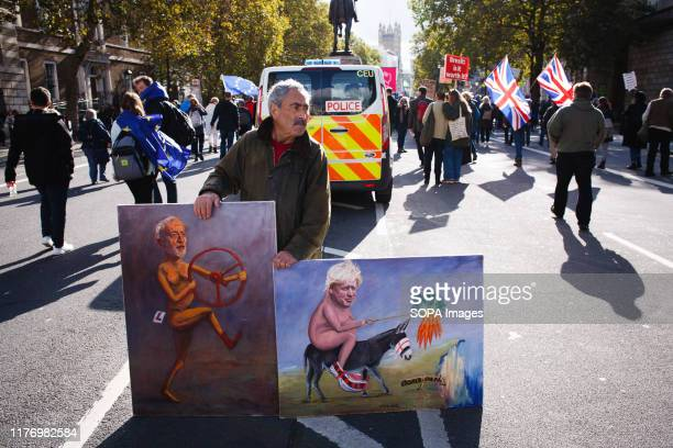 Political artist Kaya Mar stands with two of his paintings at Whitehall during the protest A mass 'Together for the Final Say' march organised by the...