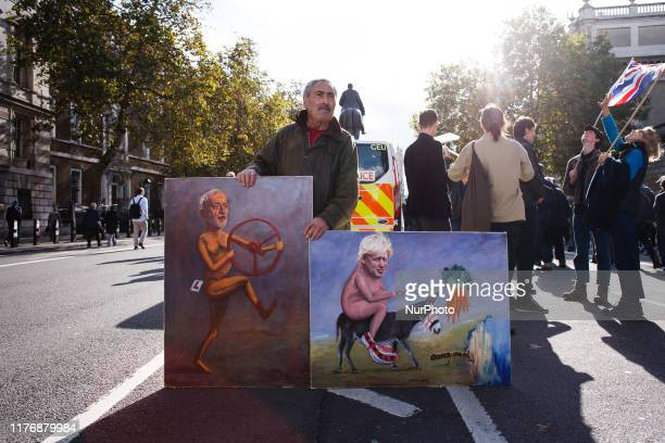 Political artist Kaya Mar stands with two of his paintings on Whitehall during the mass 'Together for the Final Say' march organised by the 'People's...