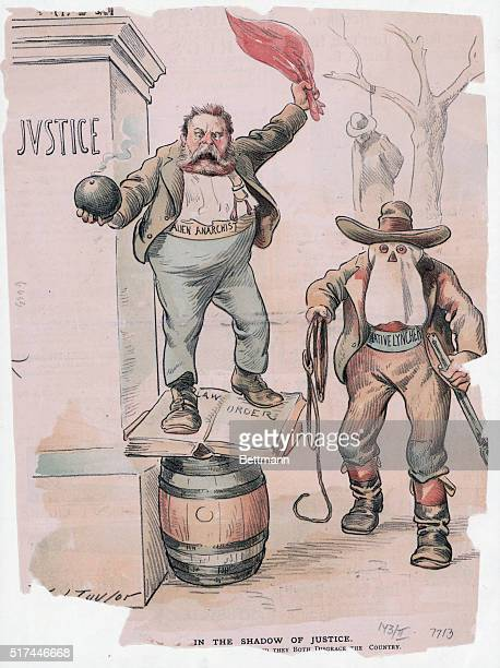 Political cartoon by Taylor entitled 'In The Shadow of Justice' Depicts the Alien Anarchist holding a bomb in one hand and a waving a red...