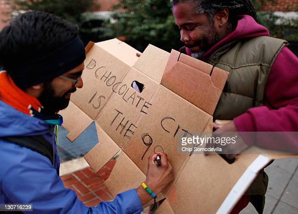 Political organizer and activist Netfa Freeman gets help with a handmade sign while marching with Howard University alumni students faculty and...